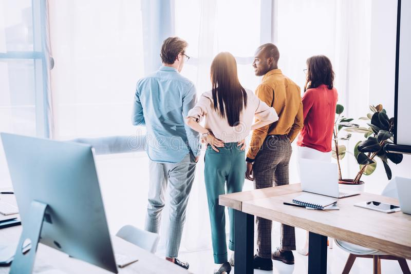 back view of multiethnic business colleagues looking out window royalty free stock image