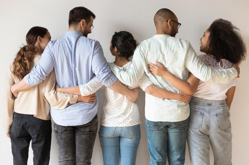 Back view of happy international young people stand hugging royalty free stock photo