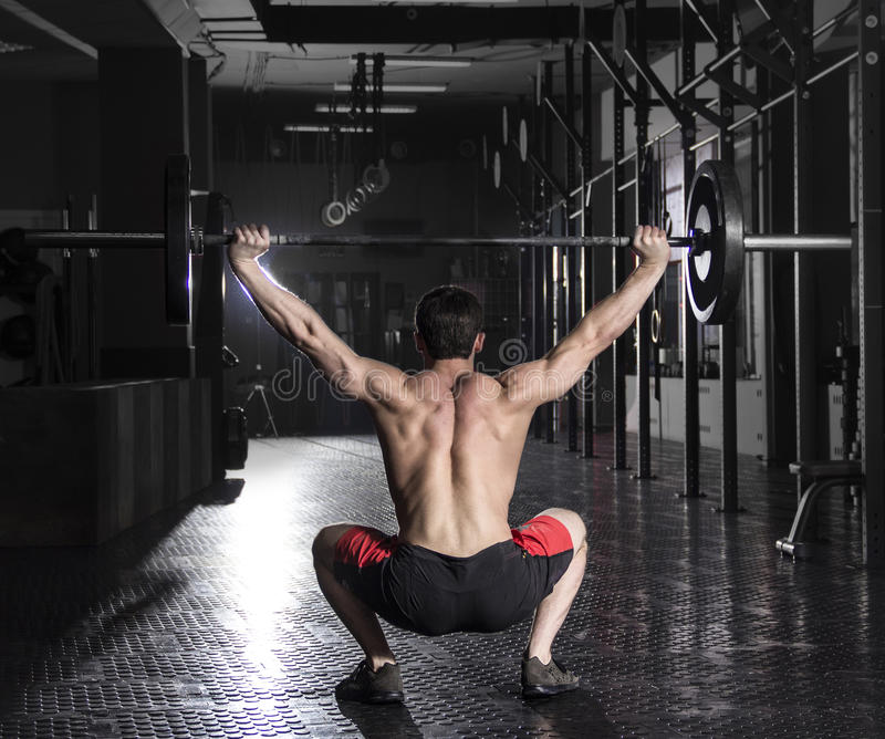 Back view of muscular athlete doing the crossfit exerise in the stock photo