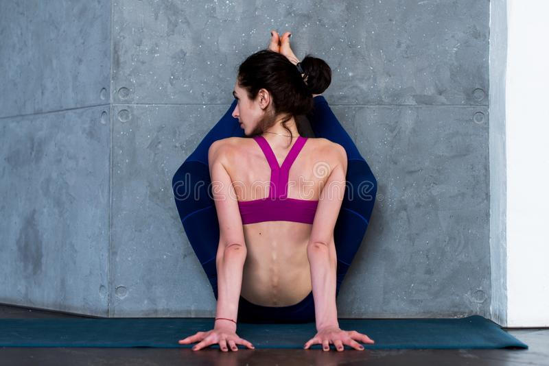 Back view of muscular young woman doing advanced stretching exercise with wall performing variation of upward facing. Forward bend pose during yoga routine royalty free stock photo