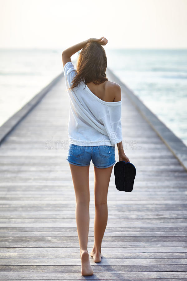 Free Back View Of Young Beautiful Woman Walking On The Pier Stock Photos - 75478773
