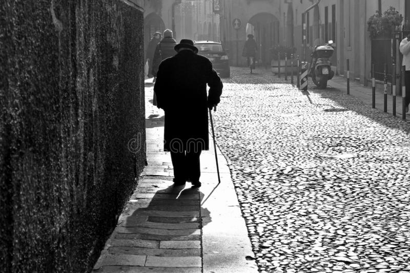 Back view of old man with hat and stick walking alone in city street during cold winter day in italian town stock photos