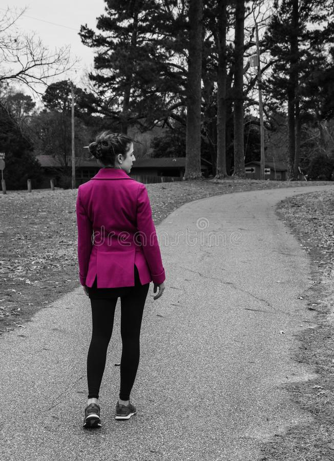 Back view, partial profile, black and white of young woman wearing bright pink coat jacket, braided hair, walking on path. Black white back, profile view of stock photo