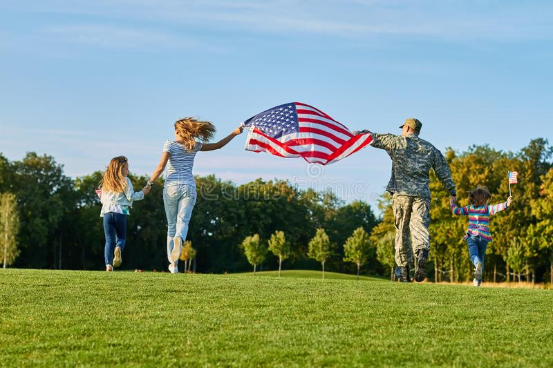 Back view, patriotic family moving with huge american flag. stock image