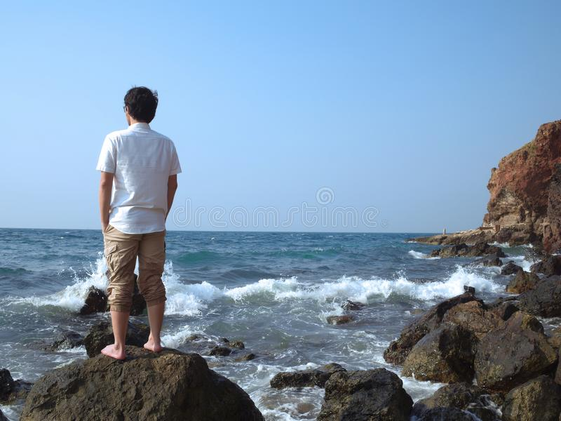 Back view of pensive lonely young Asian man standing on the rock of seashore. stock photos