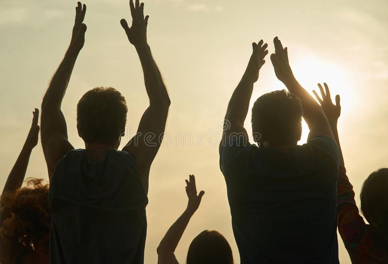 Back view people applauding. Silhouette clapping people against evening sun background stock image