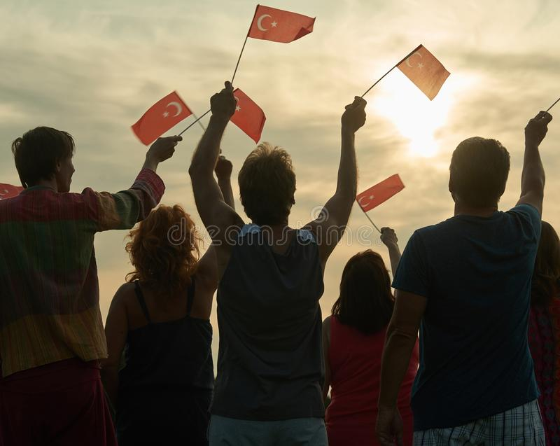 Back view people raising turkish flags. Family silhouette against sunset background royalty free stock photos