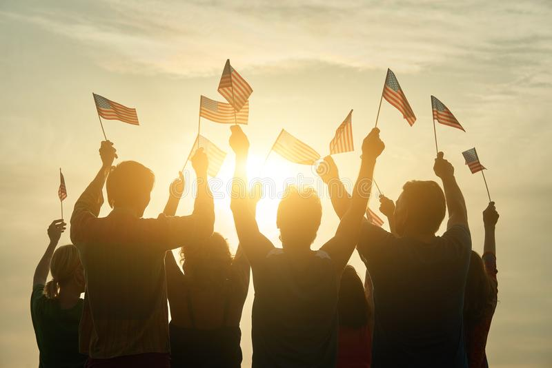 Back view people raising USA flags. Patriotic american family, rear view royalty free stock photography