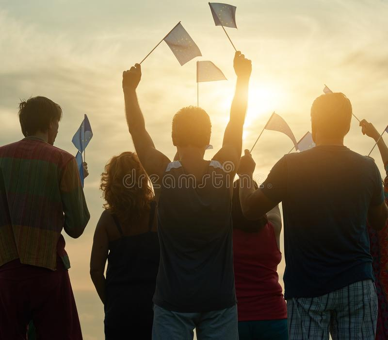 Back view people waving european flags. European family against evening sky background royalty free stock images