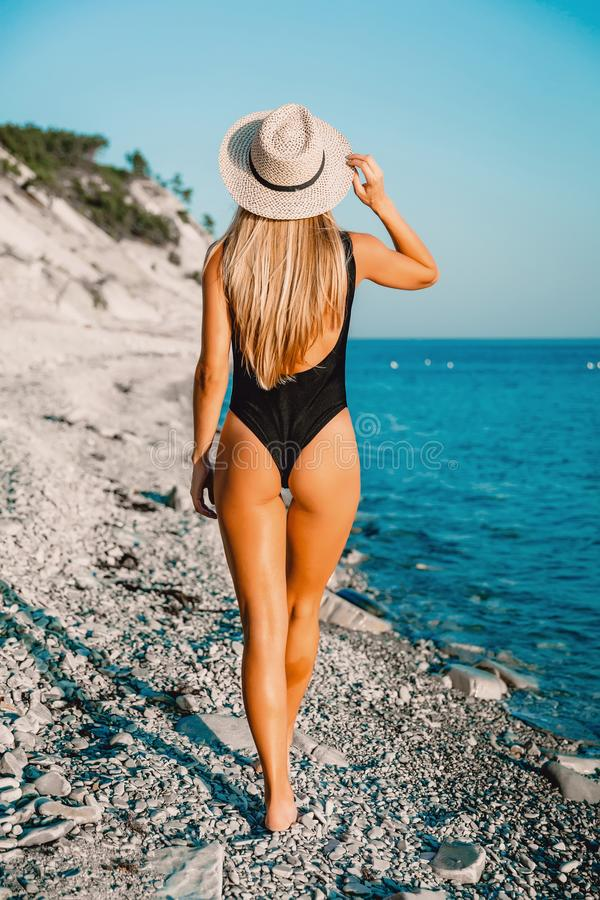 Back view of perfect woman in bikini with bonnet relaxing at sea stock photography