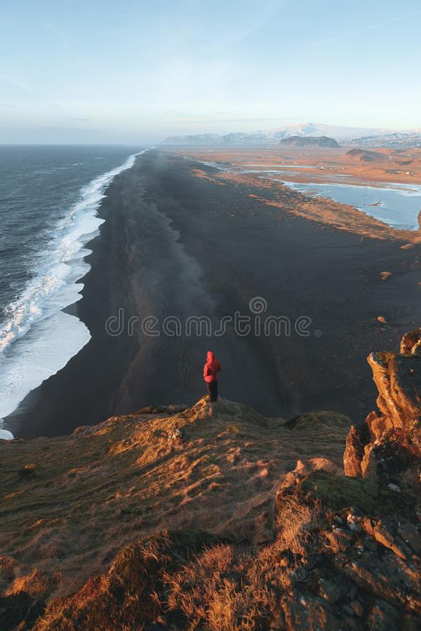 Back view of person standing on cliff and looking at majestic ocean, vik dyrholaey, reynisfjara. Beach, iceland royalty free stock image