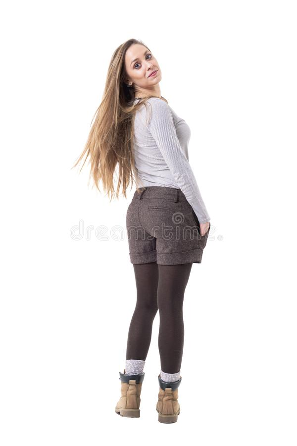 Back view of playful young happy hipster girl with long blonde hair turning and looking back at camera. royalty free stock photo