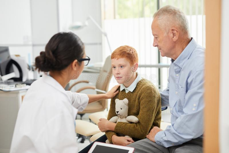 Nurse Comforting Boy in Doctors Office stock images