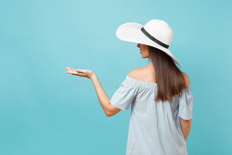 Back view portrait of elegant fashion young woman in white summer large wide brim sun hat, dress put hands on head stock images