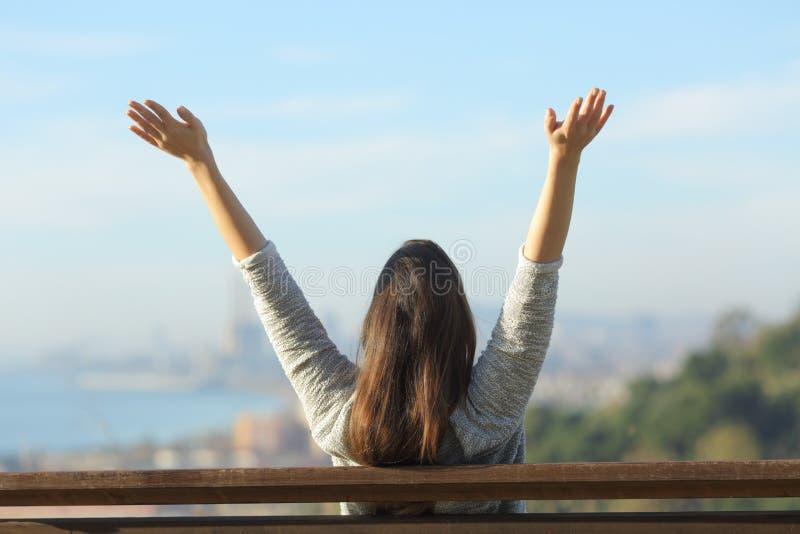 Happy woman raising arms looking at horizon royalty free stock photo
