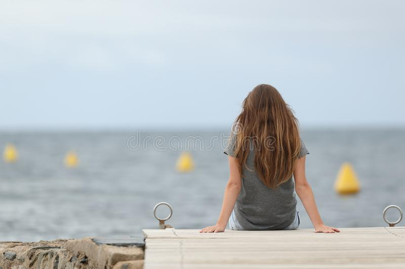 Back view of a lonely teen looking at the ocean stock image