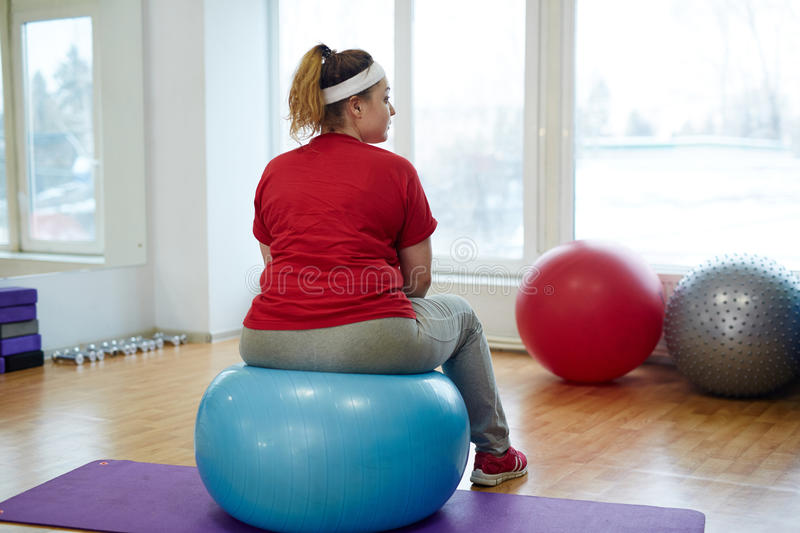 Back View Portrait of Obese Woman on Fitness ball. Back view portrait of overweight woman working out in fitness studio: bouncing on big fitness ball looking royalty free stock photo