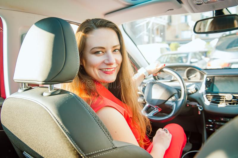 Back view Portrait of smiling business lady, caucasian young woman driver looking at camera and smiling over her shoulder while royalty free stock images
