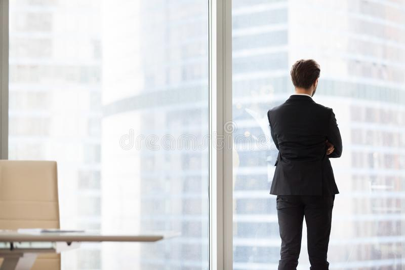 Back view portrait of successful businessman standing by window stock photo
