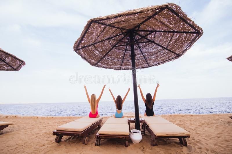 Back view portrait of three women friends sitting and resting in lounge chairs with umbrella on the sea beach. Rear view. royalty free stock image