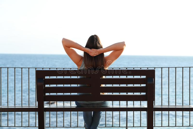 Woman relaxing on the beach sitting on a bench stock photography