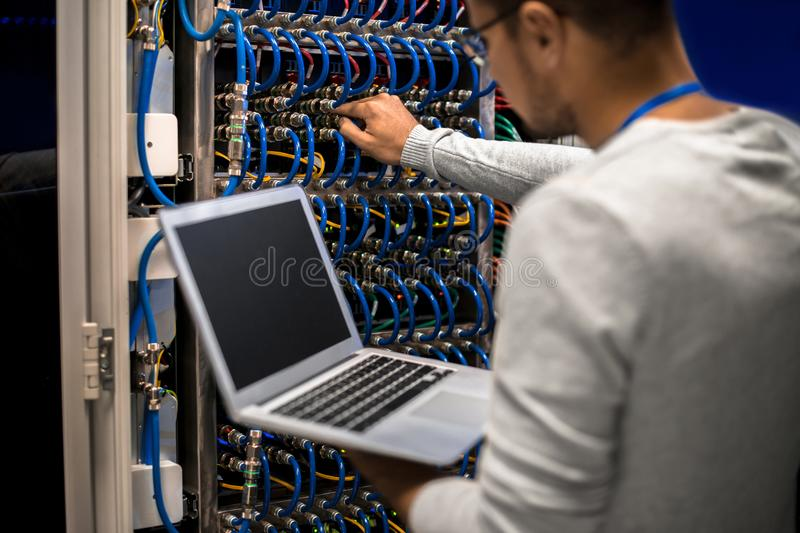 Network Engineer Connecting Servers. Back view portrait of young man working with supercomputer connecting blade server cables and checking data on laptop royalty free stock photo