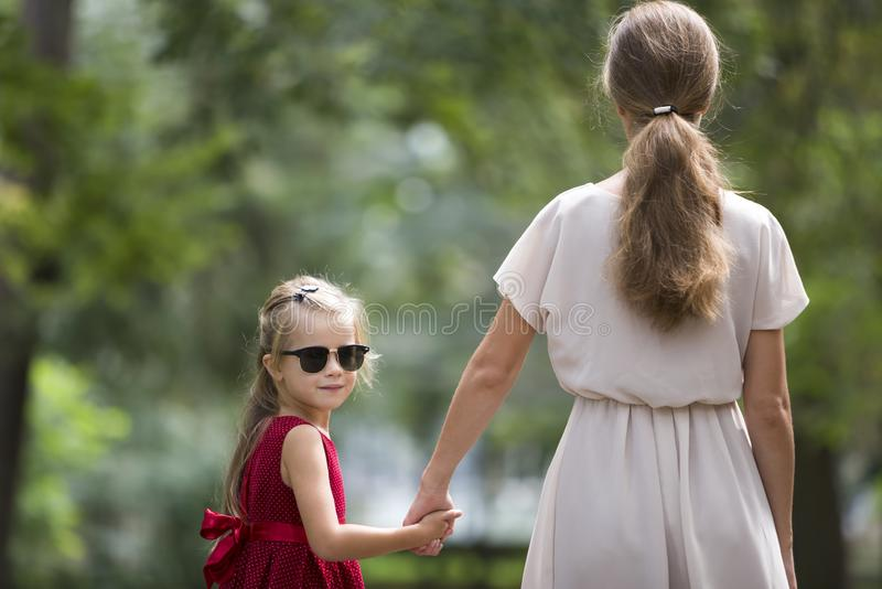 Back view of pretty small blond long-haired child girl in sunglasses and fashionable red dress holding trustingly hand of young stock photos