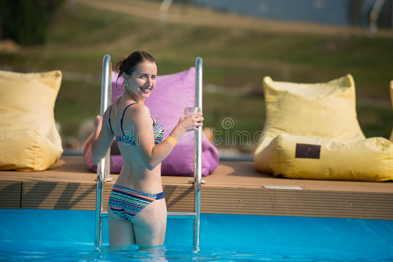 Back view pretty woman in swimwear is going out of the pool, turned around. And smiling, holding a glass of drink royalty free stock photos
