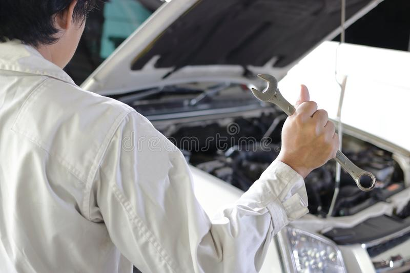 Back view of professional young mechanic man in uniform holding wrench against car in open hood at the repair garage. Back view of professional young mechanic stock image