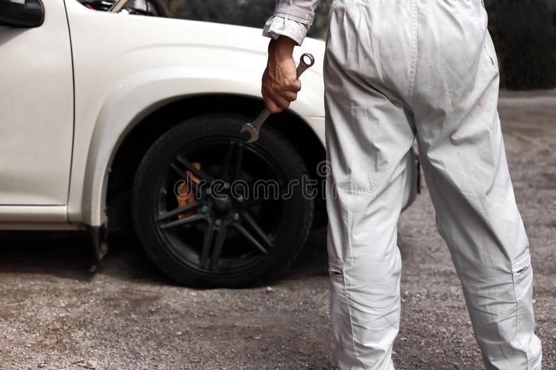 Back view of professional young mechanic man in uniform holding wrench against car in open hood at the repair garage. Back view of professional young mechanic stock photo