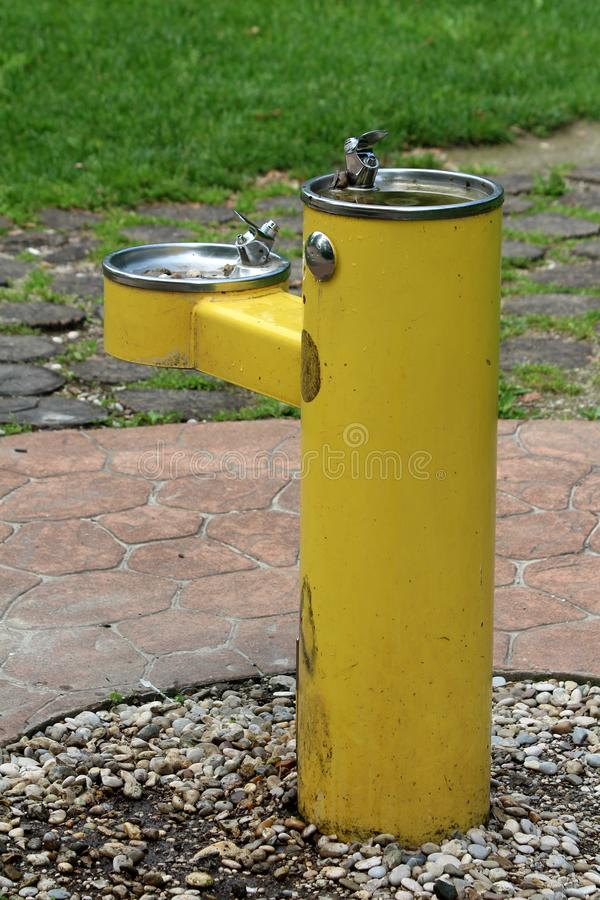 Back view of public park old dilapidated yellow two level drinking fountain for adults and children surrounded with gravel and royalty free stock photography
