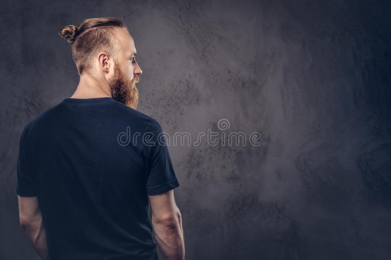 Back view of a redhead bearded man dressed in a black t-shirt. Isolated on the dark textured background. Back view of a redhead bearded man dressed in a black t stock images