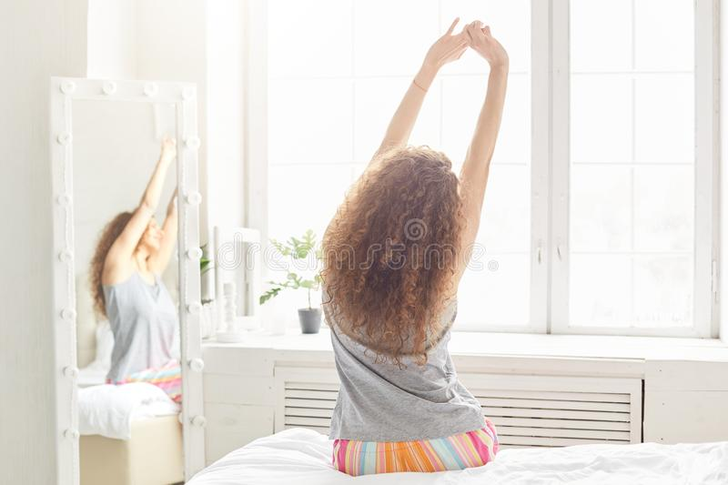 Back view of relaxed woman stretches in bed, poses near window against cozy bedroom interior, wakes up in morning after good sleep stock images