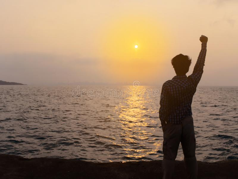 Back view of relaxed young Asian man raising hands at sea shore with sunset background royalty free stock images