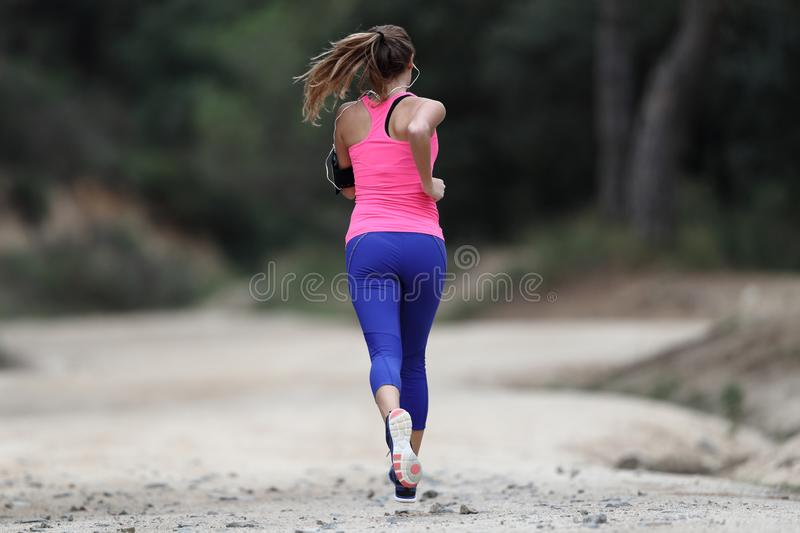 Back view of a runner woman running outdoors stock images