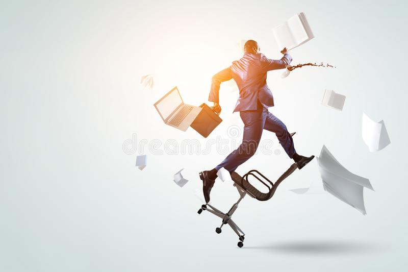 Back view of running black businessman with briefcase and falling around documents, books, laptop, chair royalty free stock photos