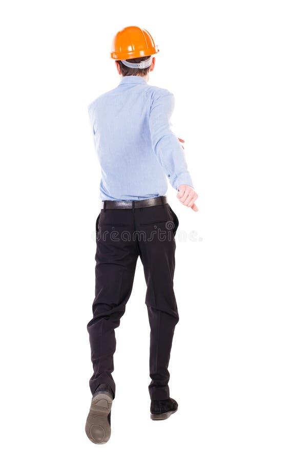 Back view of running engineer in helmet. Walking guy in motion. stock photo