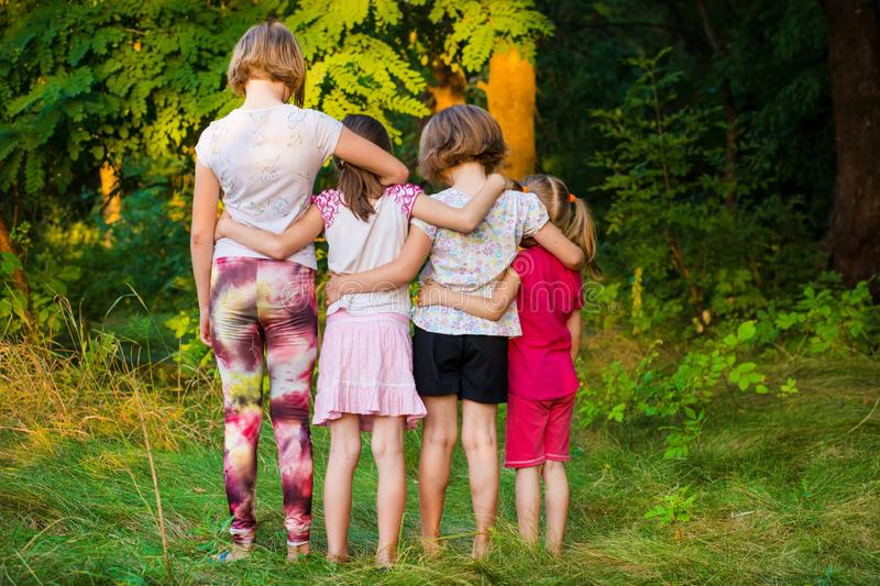 Back view of sad children stand in hug together in summer stock photo