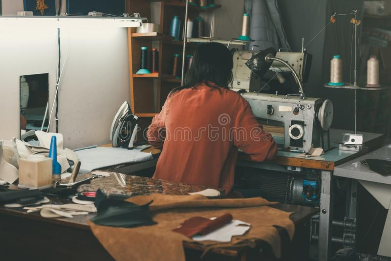 Back view of seamstress working with sewing machine and leather at shoemaker. Workshop royalty free stock photos