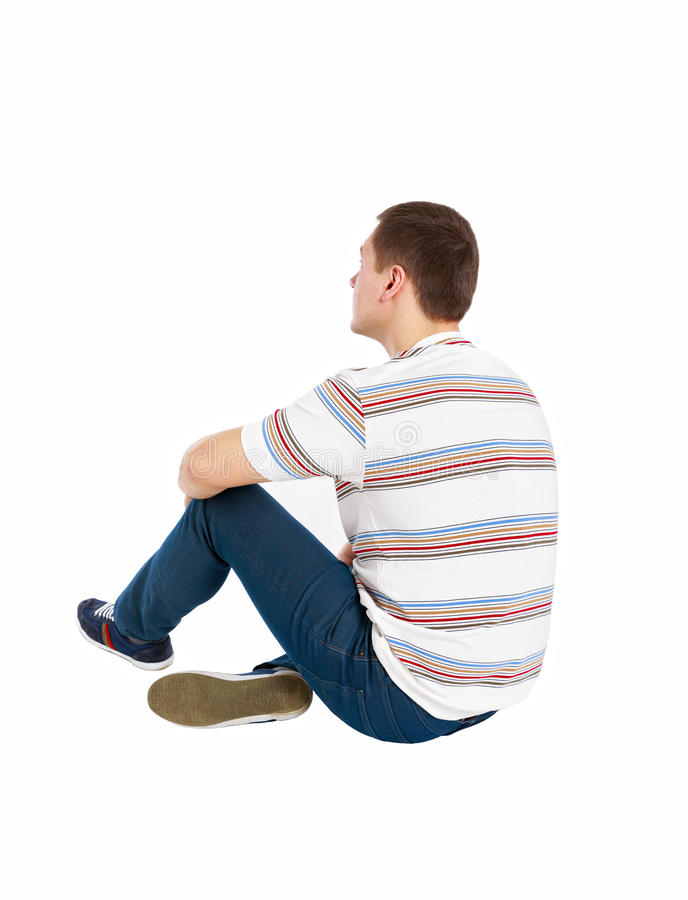 Back view of seated handsome man in t-shirt and jeans looking up stock image