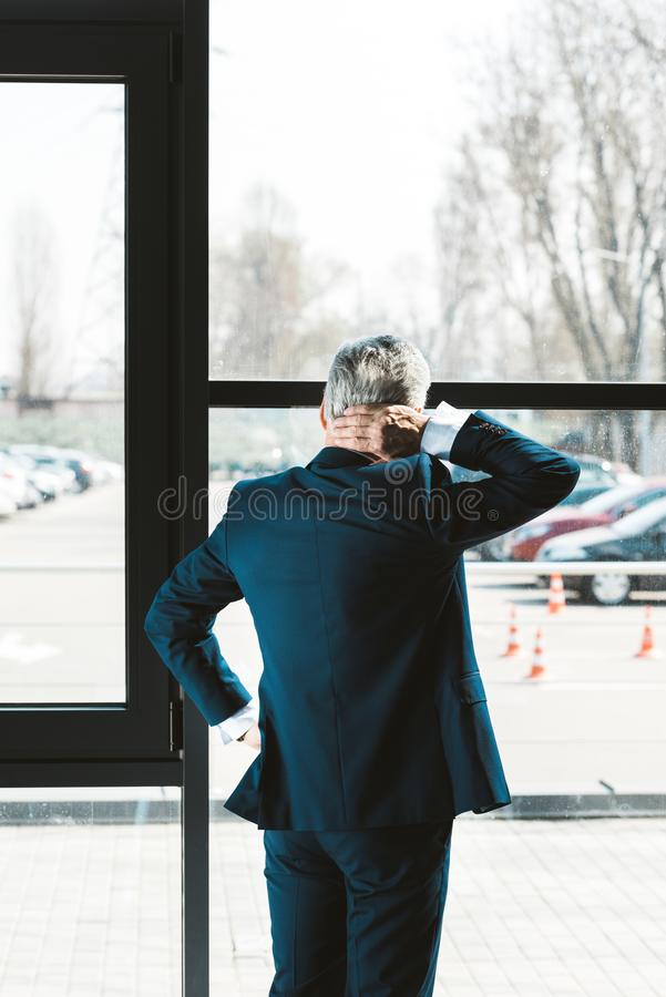 Back view of senior businessman. In formal wear looking at window royalty free stock photo