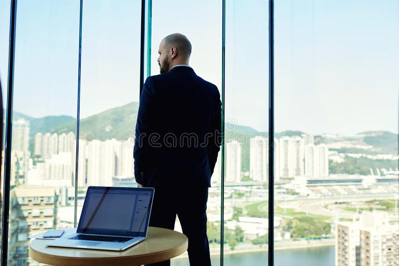 Back view of a serious man intelligent lawyer is thinking about the future of an important trial. Male CEO is standing near big office window with view on stock image