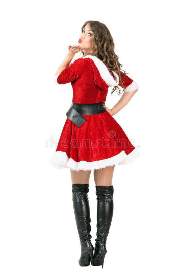 Back view of attractive young female Santa Claus blowing a kiss at camera royalty free stock photo