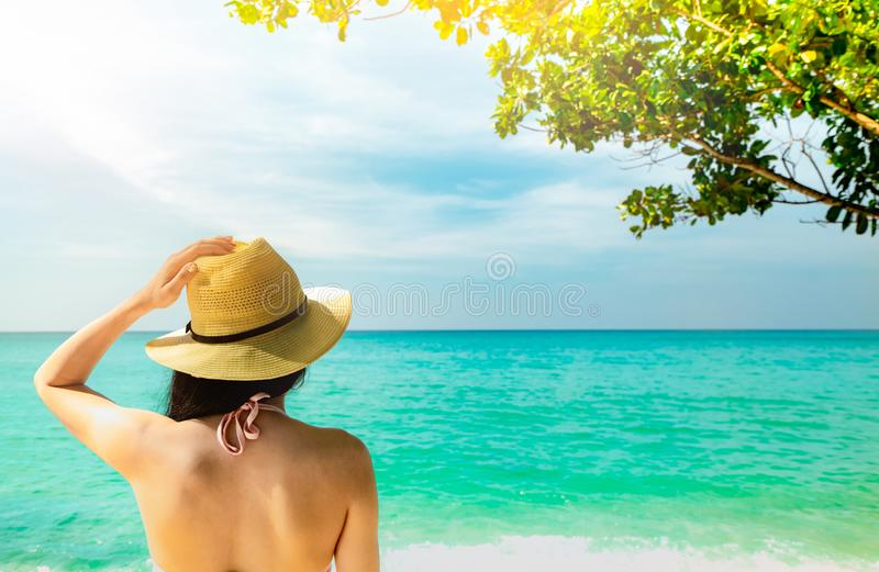 Back view of and happy young Asian woman wear straw hat relaxing and enjoy holiday at tropical paradise beach. Girl standing. At the beach and looking the sea stock photo