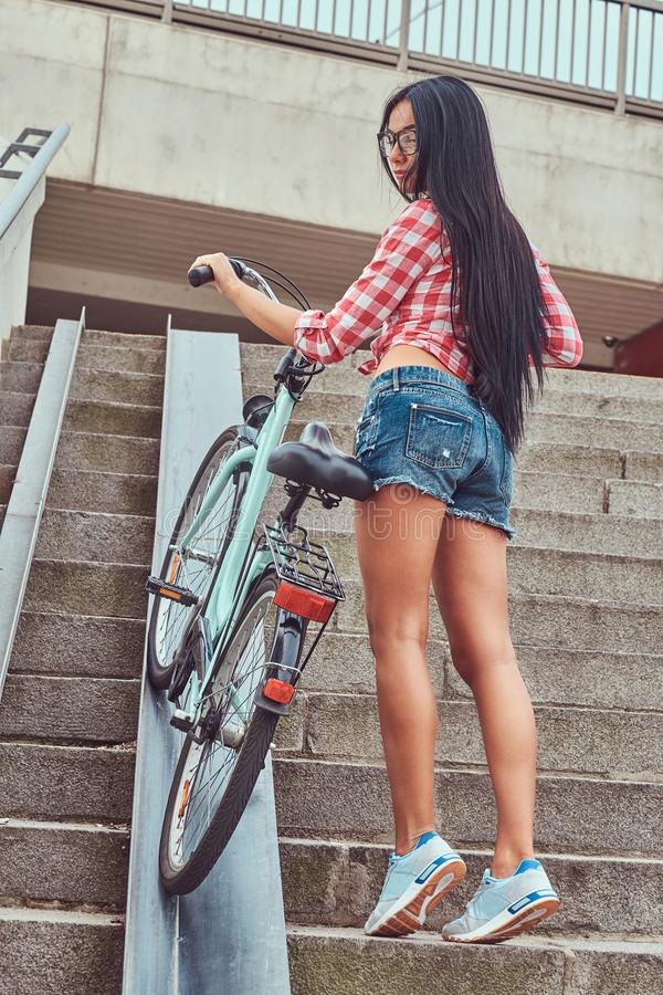 Back view of a slim female dressed a pink flannel shirt and denim shorts, climbs the stairs with a bike. stock images