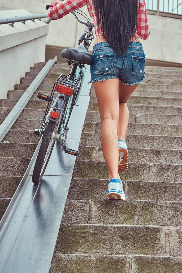 Back view of a slim female dressed a pink flannel shirt and denim shorts, climbs the stairs with a bike. stock photography