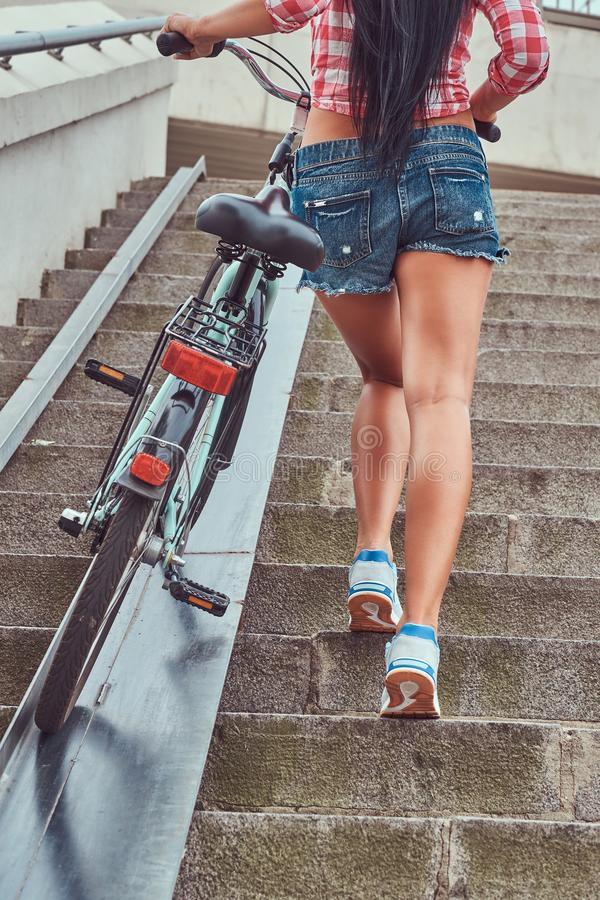 Back view of a slim female dressed a pink flannel shirt and denim shorts, climbs the stairs with a bike. royalty free stock image