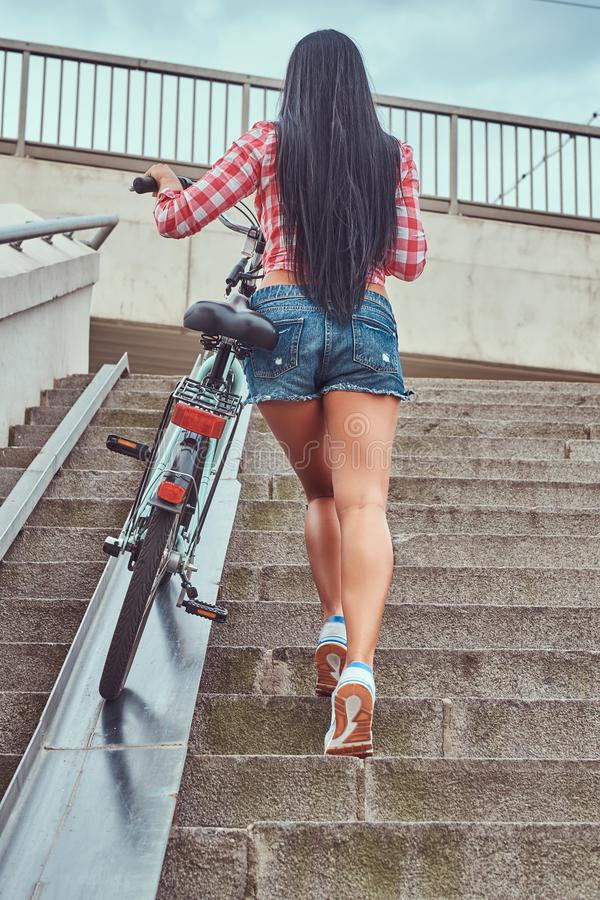 Back view of a slim female dressed a pink flannel shirt and denim shorts, climbs the stairs with a bike. royalty free stock photo