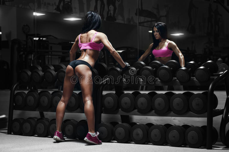 Back view of young brunette woman resting in the gym and le royalty free stock photography