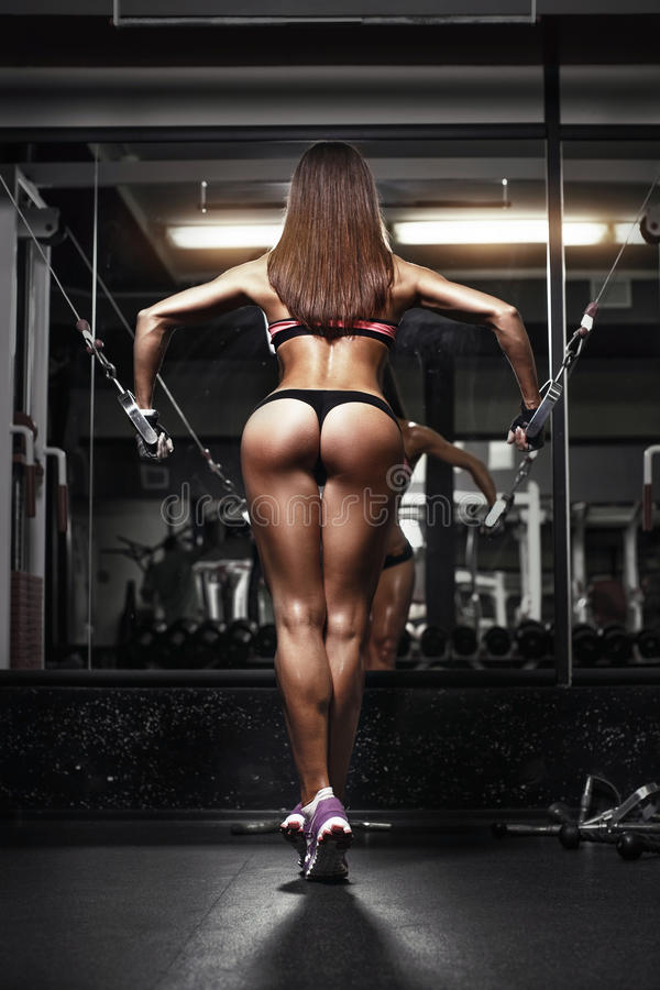 Back view of young brunette woman workout in the gym stock photography